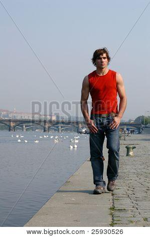 Junge sexy Mann zu Fuß entlang der Damm in Prag, Tschechische Republik.