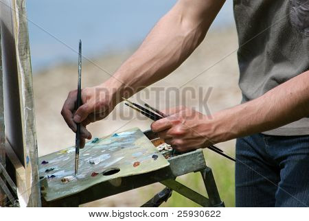Artist's hands with brushes mixing colors