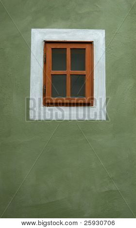 Small window on the green wall in Cesky Krumlov, Czech Republic.