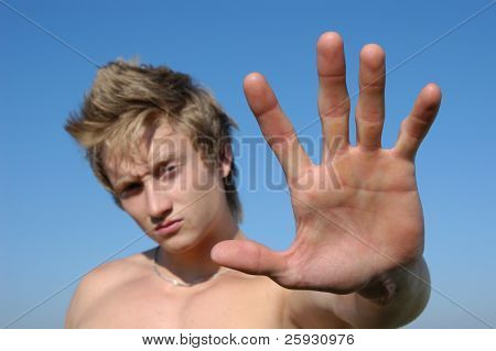 Stop! Young shirtless man holding his palm out saying 'Stop' or 'No' - palm in the focus