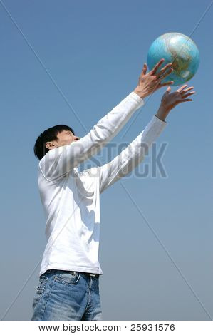 Young Asian man playing with a terrestrial globe