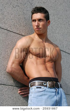 Shirtless muscular male model in front of the granite block wall