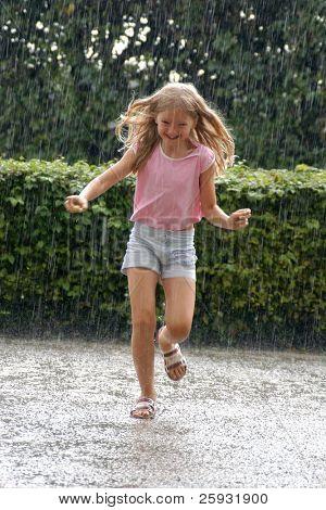Niña corriendo en la fuerte lluvia en el Parque