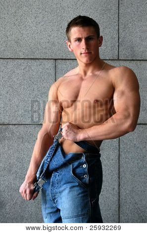 Young sexy muscular worker taking his coverall off
