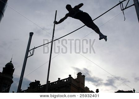 Silhouetted athlete clearing the bar during a pole vault event