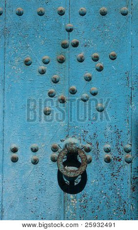 Moroccan blue door with an old knocker in Chefchaouen, Morocco