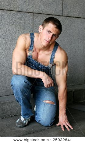 Sitting young sexy muscular worker in a blue coverall