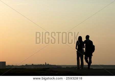 Silhouetted loving couple walking at sunset