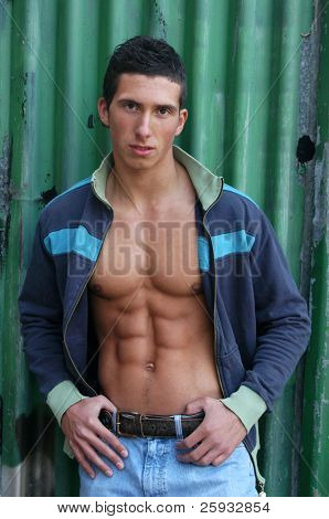 Muscular male model in an undone jacket in front of the crimping metal wall