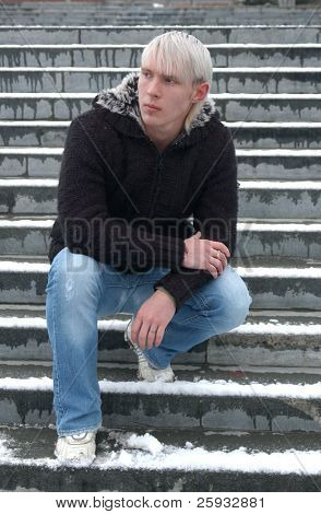 Young blond man sitting on the snow-cowered stairs
