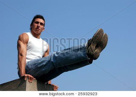 muskuläre Turner in einem weißen Tank Top hält seine Beine vor
