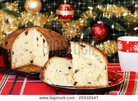 Panettone, Whole And Sliced, In Front Of A Festive Christmas Tree.