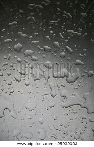 Rain drops on the gray metal surface