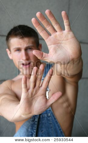 Young sexy man holding his palms out saying 'Stop' or 'No' - palms in focus