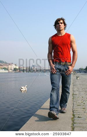Young sexy man walking along the embankment in Prague, Czech Republic
