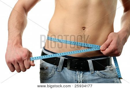Muscular man measuring his waist by meter isolated on white