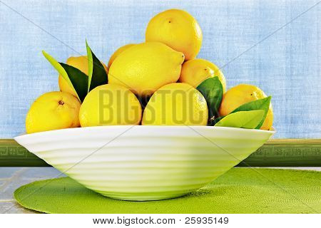 Eureka Lemons In A White China Bowl Sitting On Kitchen Counter ~ Background Is Textured Plaster Wall