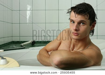 Young muscular man taking bath