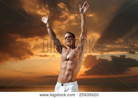 Muscular young man on the beach in the evening