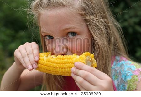 Young funny girl eating a boiled corn.