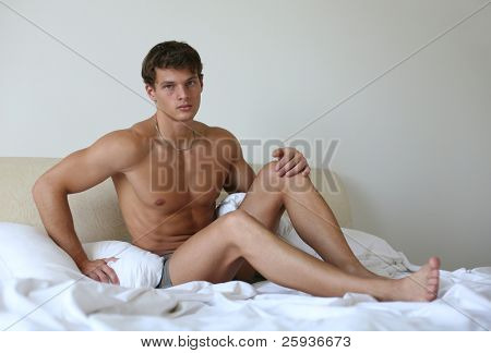 Young sexy man lying on a bed