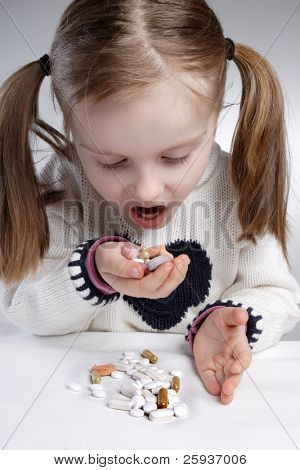 Little girl eating medication by herself