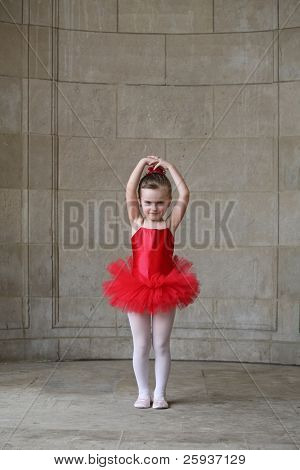 Little girl dancing in a red tutu.