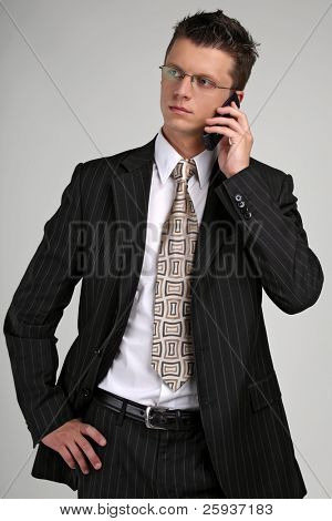 business man talking on a mobile phone in a black suit.
