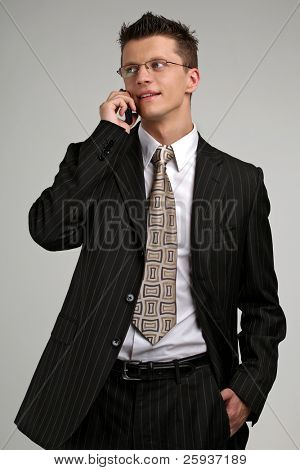 Smiling business man talking on a mobile phone in a black suit.