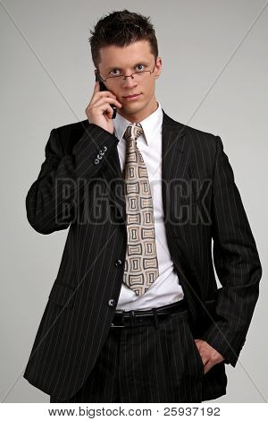 business man in glasses talking on a mobile phone in a black suit.