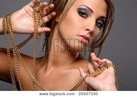 Beautiful girl with gold chain isolated on gray background.