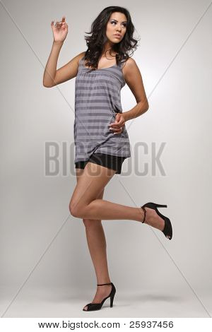 Young beautiful brunette fashion model in blue shirt and shorts on white background.