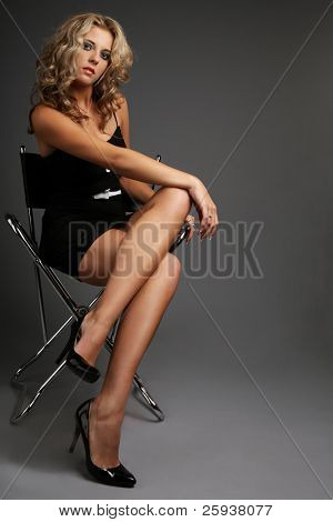 Young attractive woman in black dress posing in studio.