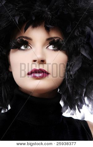 Attractive young woman in black feathers on white background.