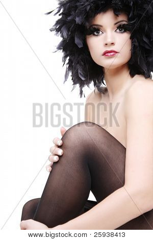Beautiful topless young woman in black feathers on white background.