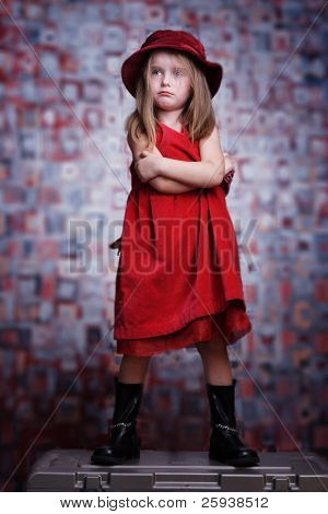 Upset cute little girl in red dress.