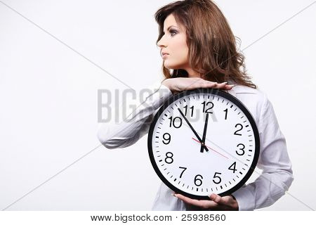 Young attractive business woman in white shirt holding clock.