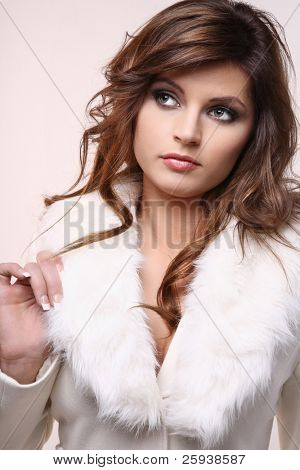 Beautiful young woman in white winter coat.