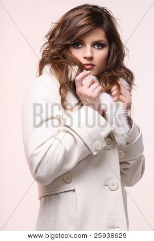 Young brunette posing in winter coat with fur.