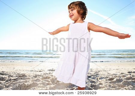 Small cute girl in white dress enjoying sunny day at the beach. Shoot against the sun.
