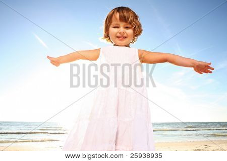 Happy little girl in white dress enjoying sunny day at the beach. Shoot against the sun.
