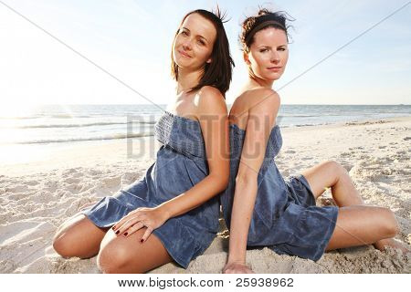Two young attractive girls enjoying friendship at the sunny beach. Shoot against the sun.