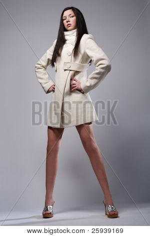 Beautiful fashion model posing in white coat.