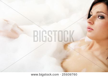 Young woman enjoys the bubble-bath in the bathtub.