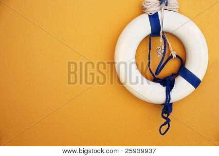 White and blue lifebuoy on orange wall.