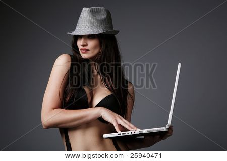 Attractive brunette in black bra paling with a laptop.