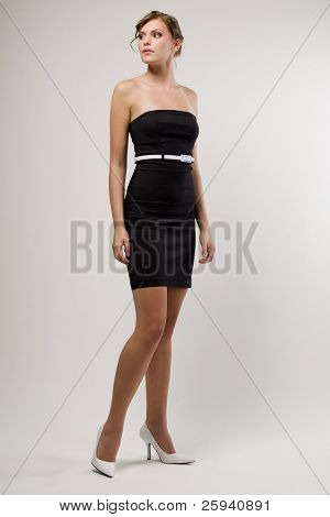 Slim young cute fashion model in black dress.