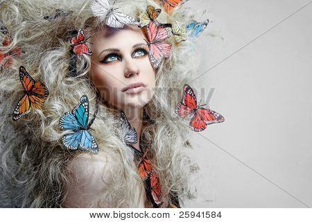Young beautiful woman with butterfly in curly blond hair.