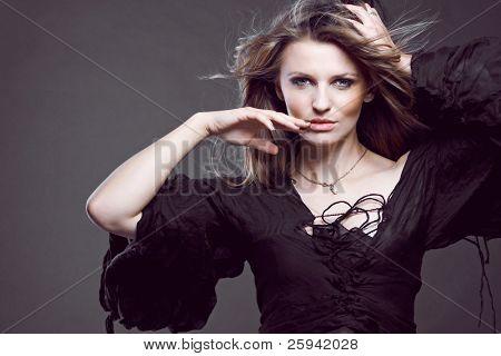 Jovem atraente modelo posando em fundo escuro.