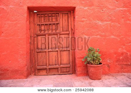Vintage red wall with old decorative stone door.